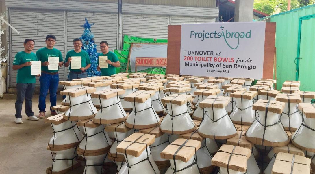 Teenage volunteers doing building work in the Philippines hand over 200 toilet bowls to a local community.